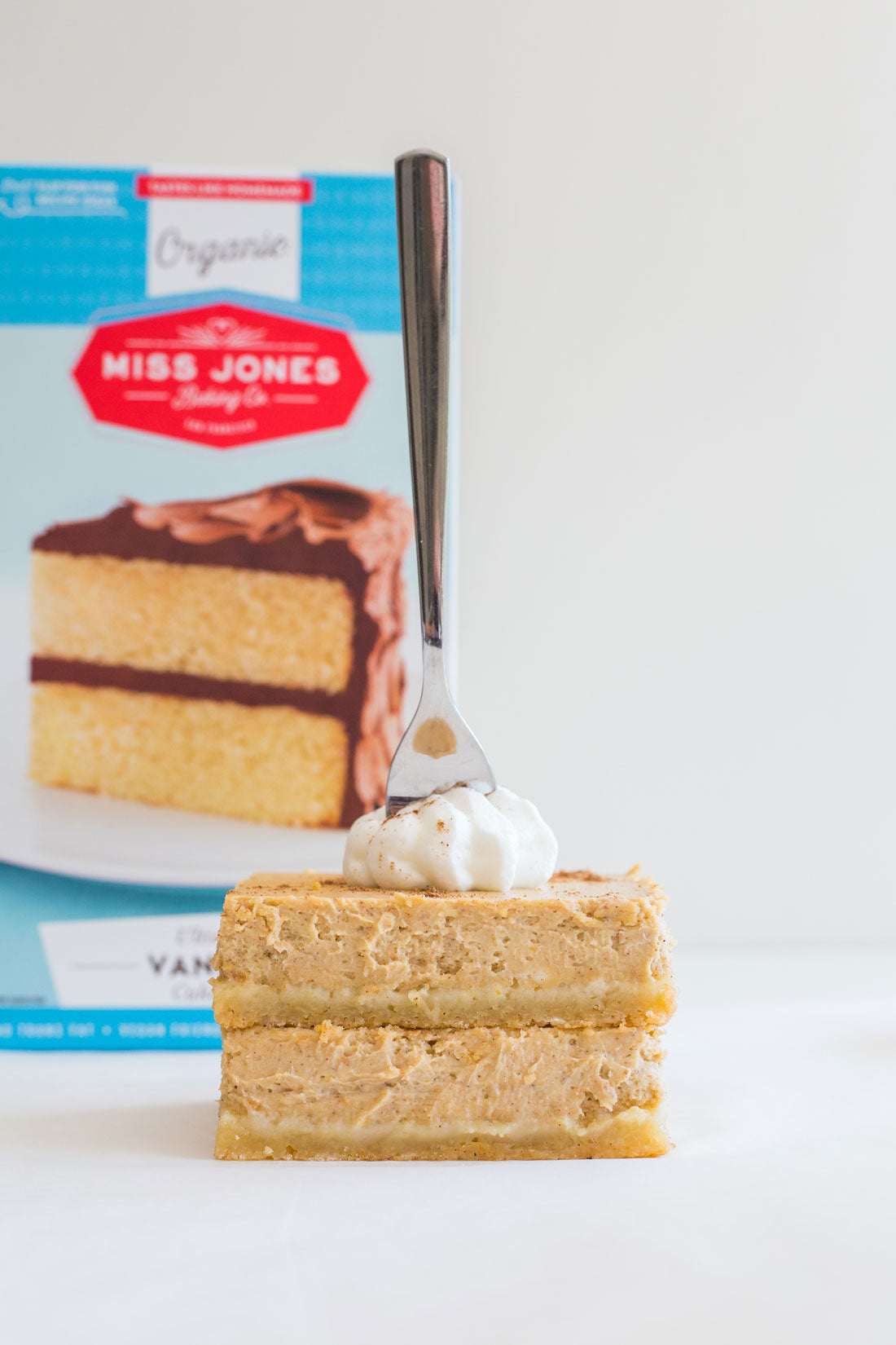 Side image of Miss Jones Baking Co Easy Pumpkin Cheesecake Bars with Miss Jones Baking Organic Vanilla Cake Mix in the background