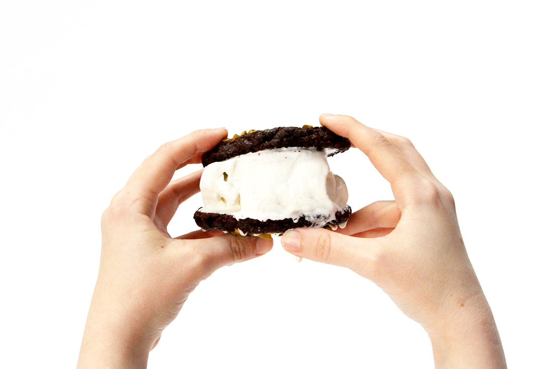 Image of two hands holding up a Miss Jones Baking Co Brownie Crisp Cookie Sandwich