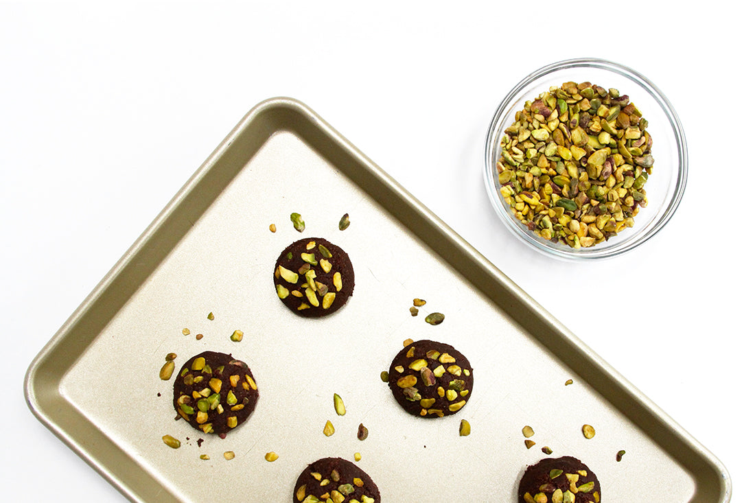 Image from above of a baking pan with five Miss Jones Baking Co Brownie Crisp Cookie Sandwiches next to a bowl of pistachios