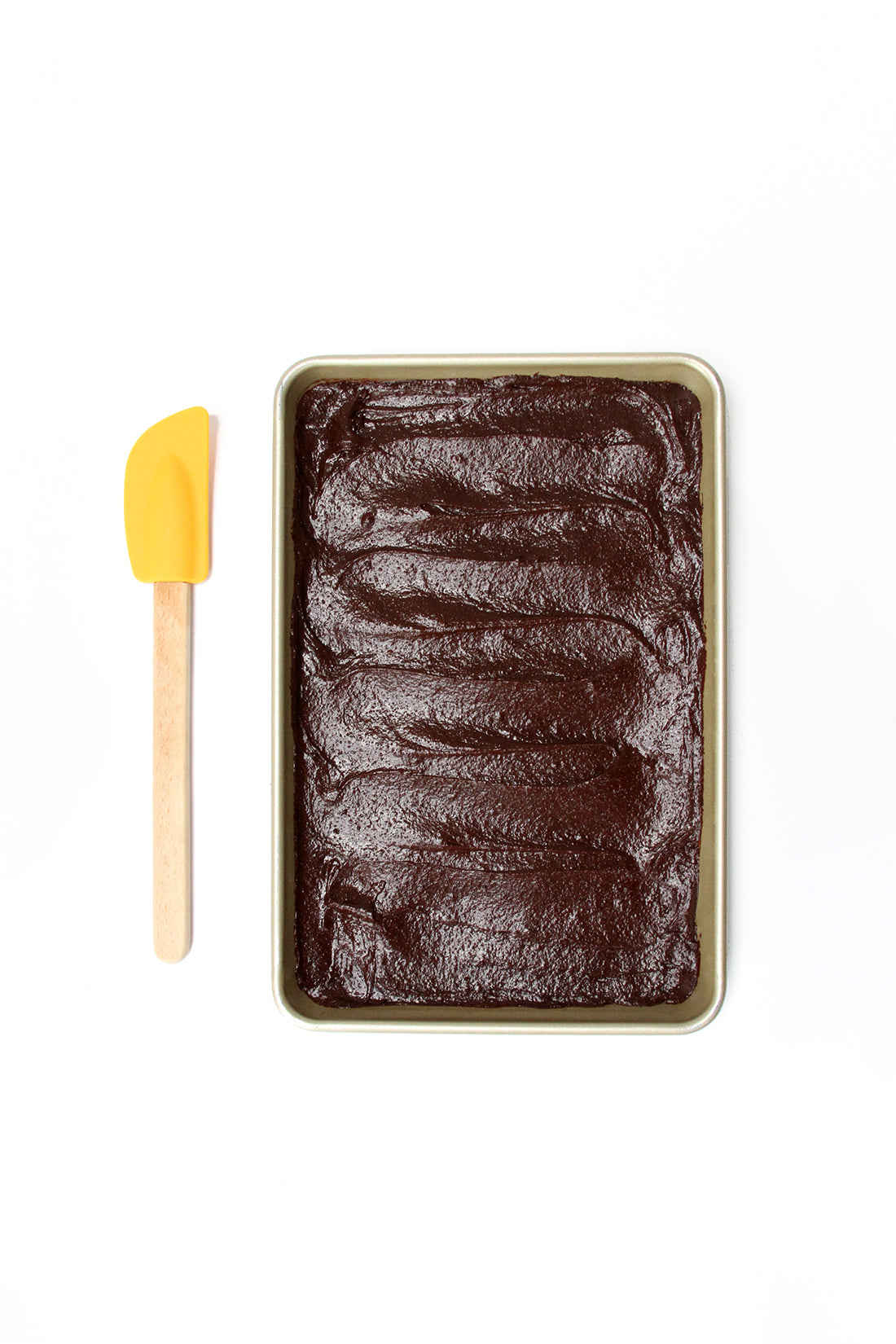Image from above of brownie batter on a baking sheet next to a yellow spatula used for Miss Jones Baking Co Coffee Break Shake