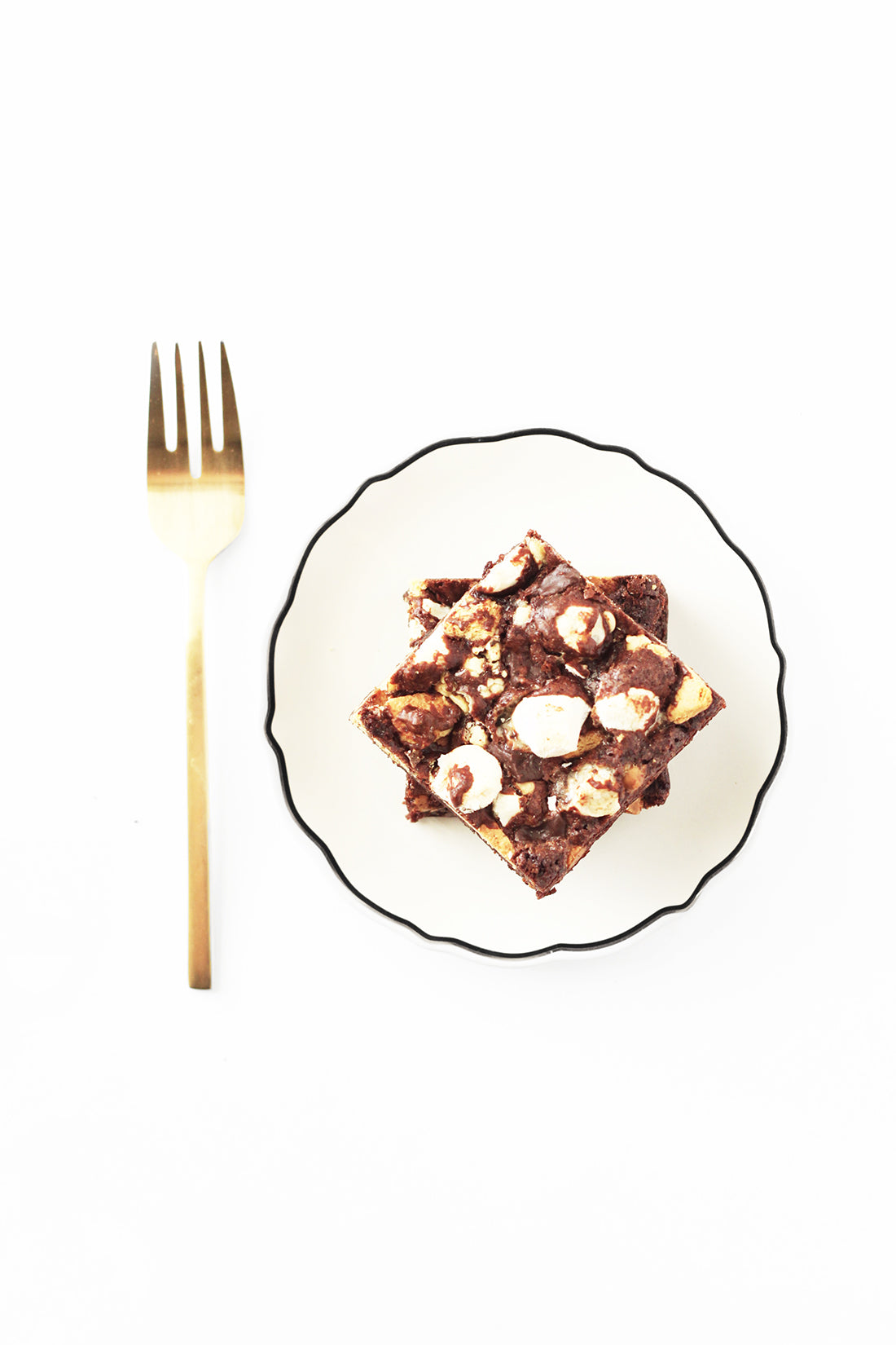 Image of two Miss Jones Baking Co Campfire Smores Brownies stacked on a plate next to a golden fork