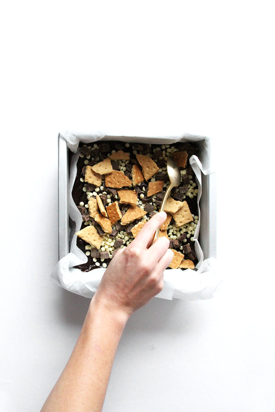 Image of Miss Jones Baking Co Campfire Smores Brownies in baking pan being topped with graham crackers