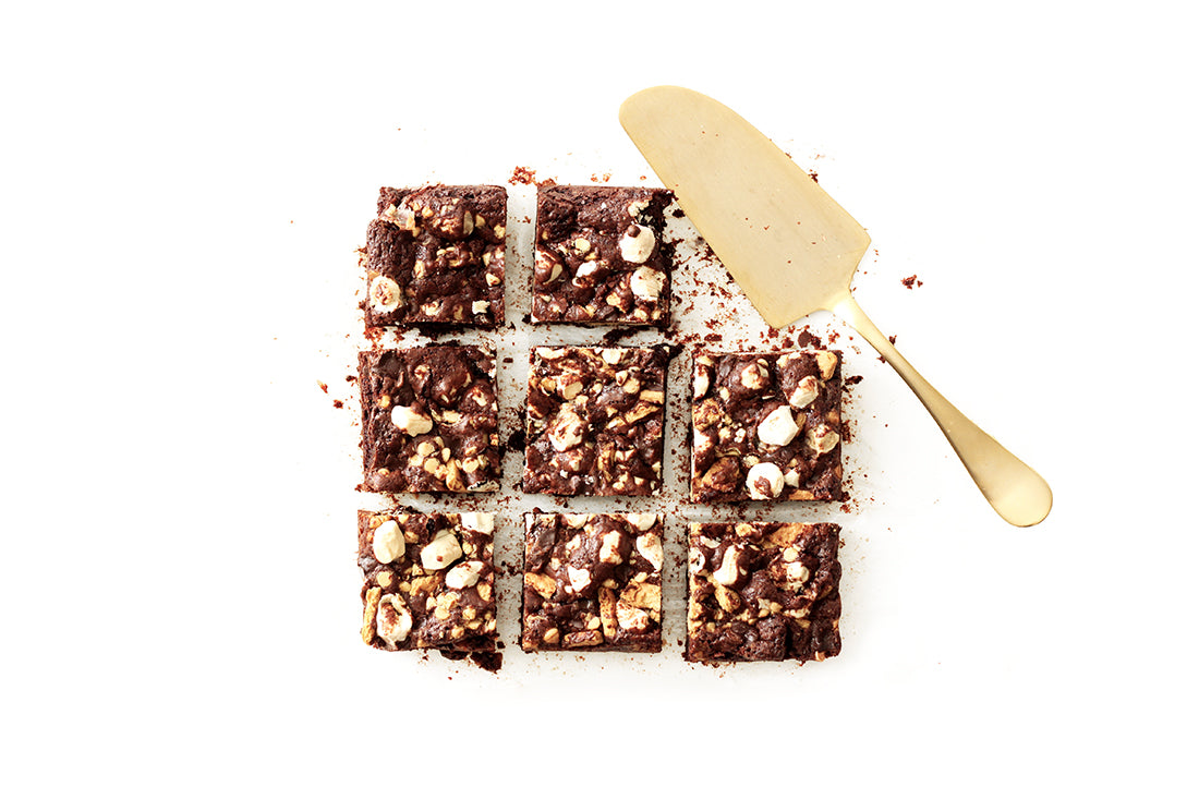 Image of eight Miss Jones Baking Co Campfire Smores Brownies in square formation with a golden utensil in place of the ninth brownie