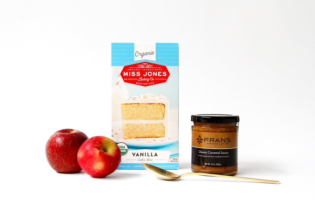 A couple of apples with a box of Miss Jones Organic Vanilla Cake mix and a tub of Fran's caramel sauce used for Miss Jones Baking Co Caramel Apple Bars