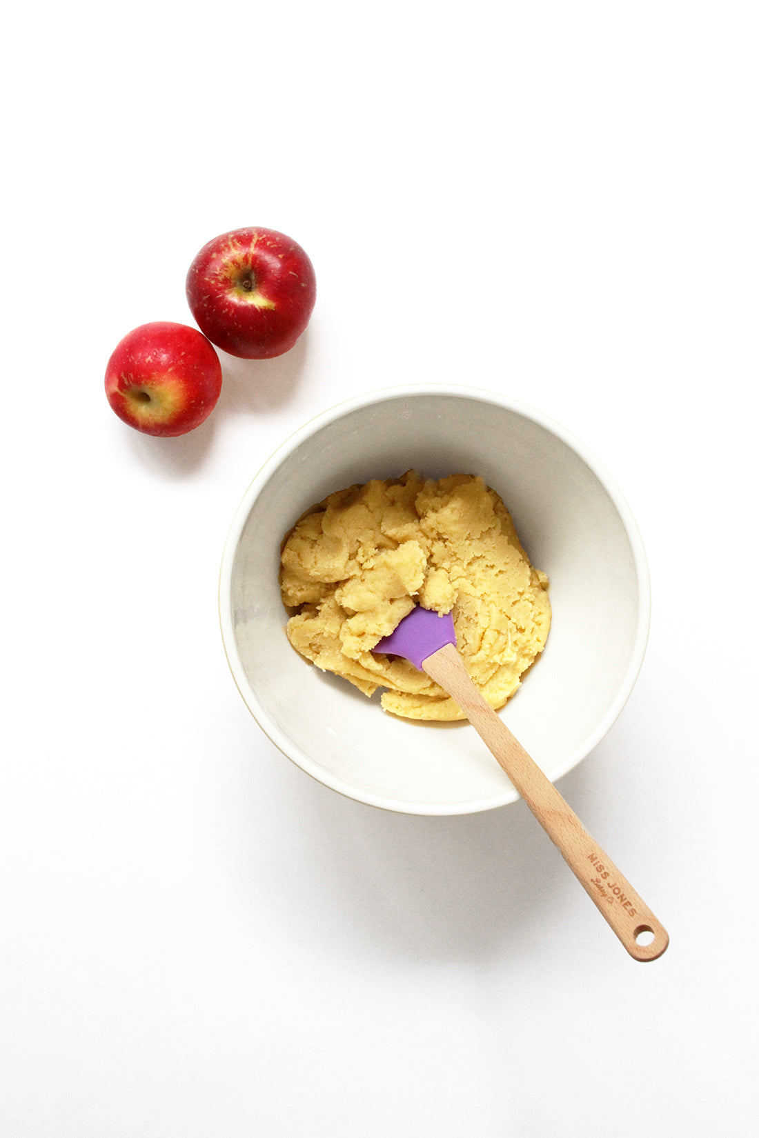Image of a mixing bowl with batter for Miss Jones Baking Co Caramel Apple Bars next to two red apples