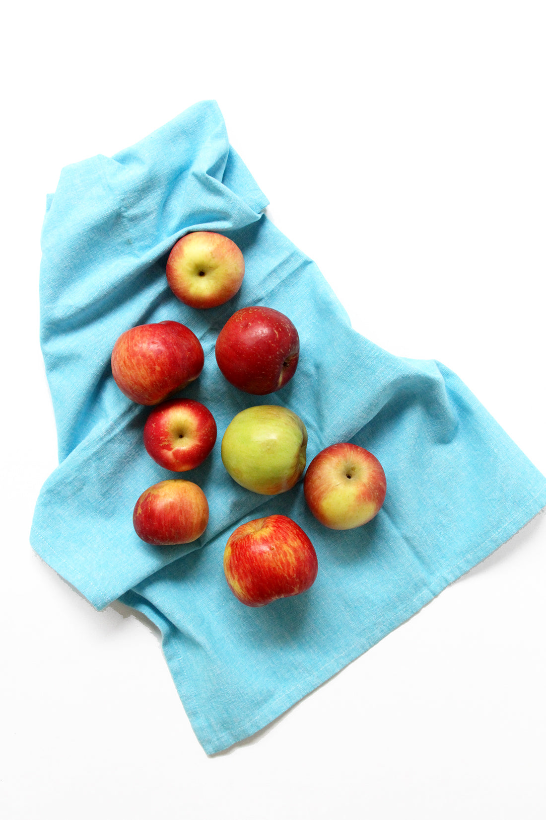 Image of eight apples on top of a blue hand towel used for Miss Jones Baking Co Caramel Apple Bars