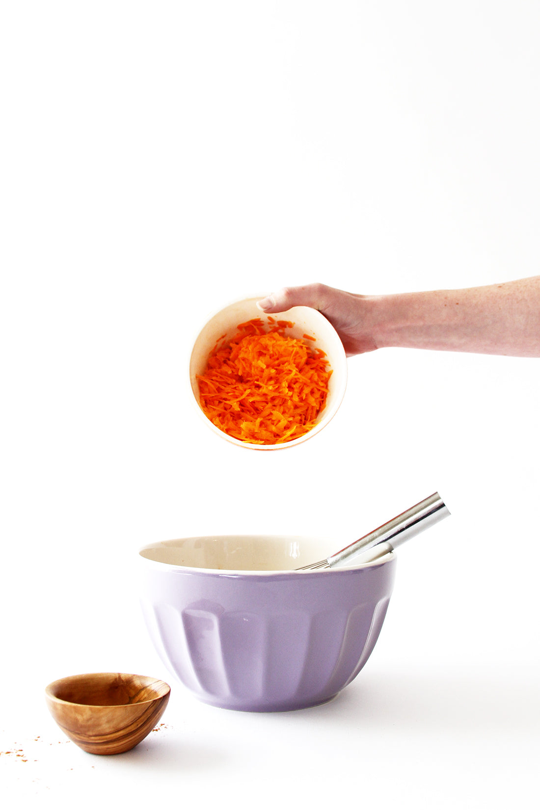 Image of shredded carrots being poured into a purple mixing bowl for Miss Jones Baking Co Carrot Spice Cake recipe