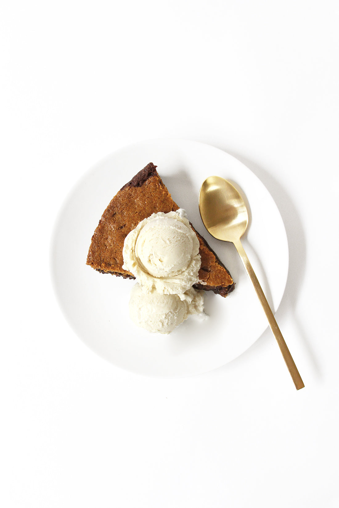 A slice of Miss Jones Baking Co Chocolate Chip Brownie Skillet on a white plate with a scoop of vanilla ice-cream on top next to spoon