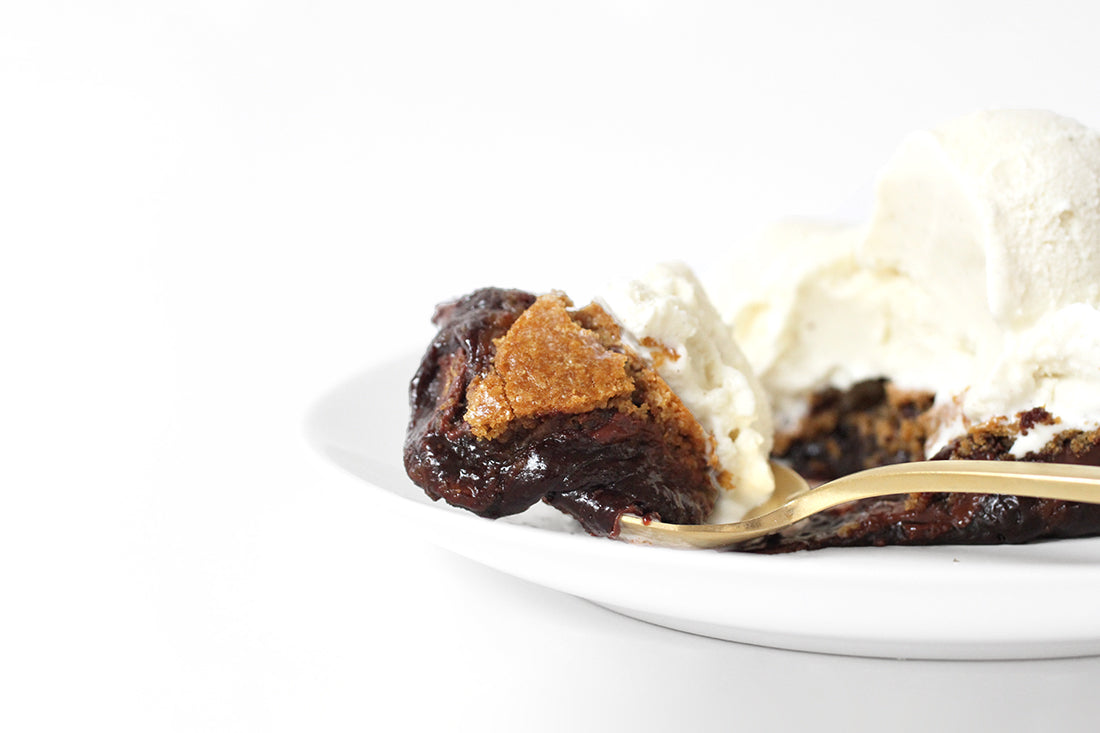 Close up image of a bite of Miss Jones Baking Co Chocolate Chip Brownie Skillet on a golden fork