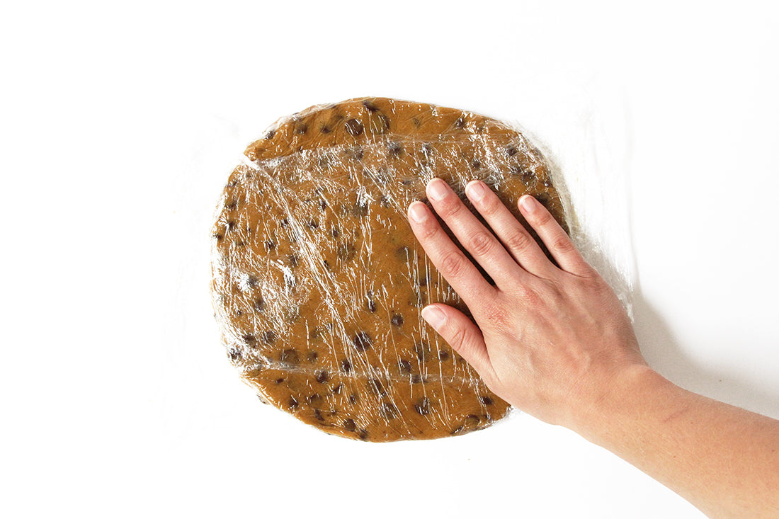 Flattened cookie dough covered in plastic wrap used for Miss Jones Baking Co Chocolate Chip Brownie Skillet