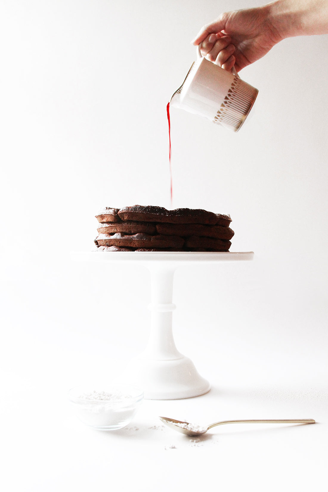 A hand pouring jam onto a stack of Miss Jones Baking Co Chocolate Cake Waffles on a cake stand