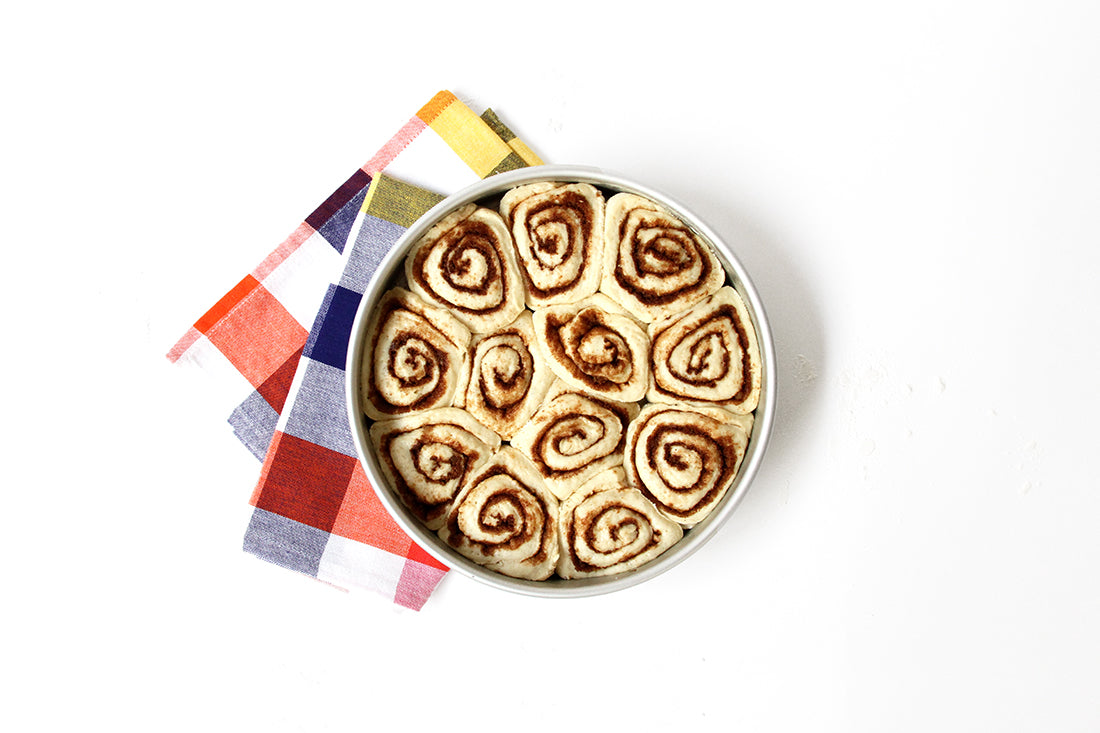 Image from above of a circular baking pan with twelve Miss Jones Baking Co Cake Mix Cinnamon Rolls