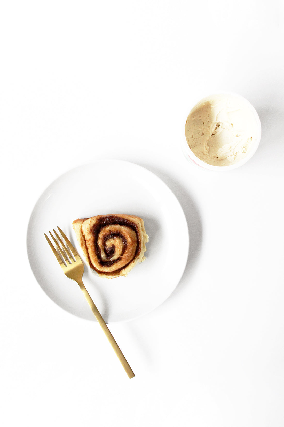 Image from above of a plate with Miss Jones Baking Co Cake Mix Cinnamon Roll next to a container of frosting