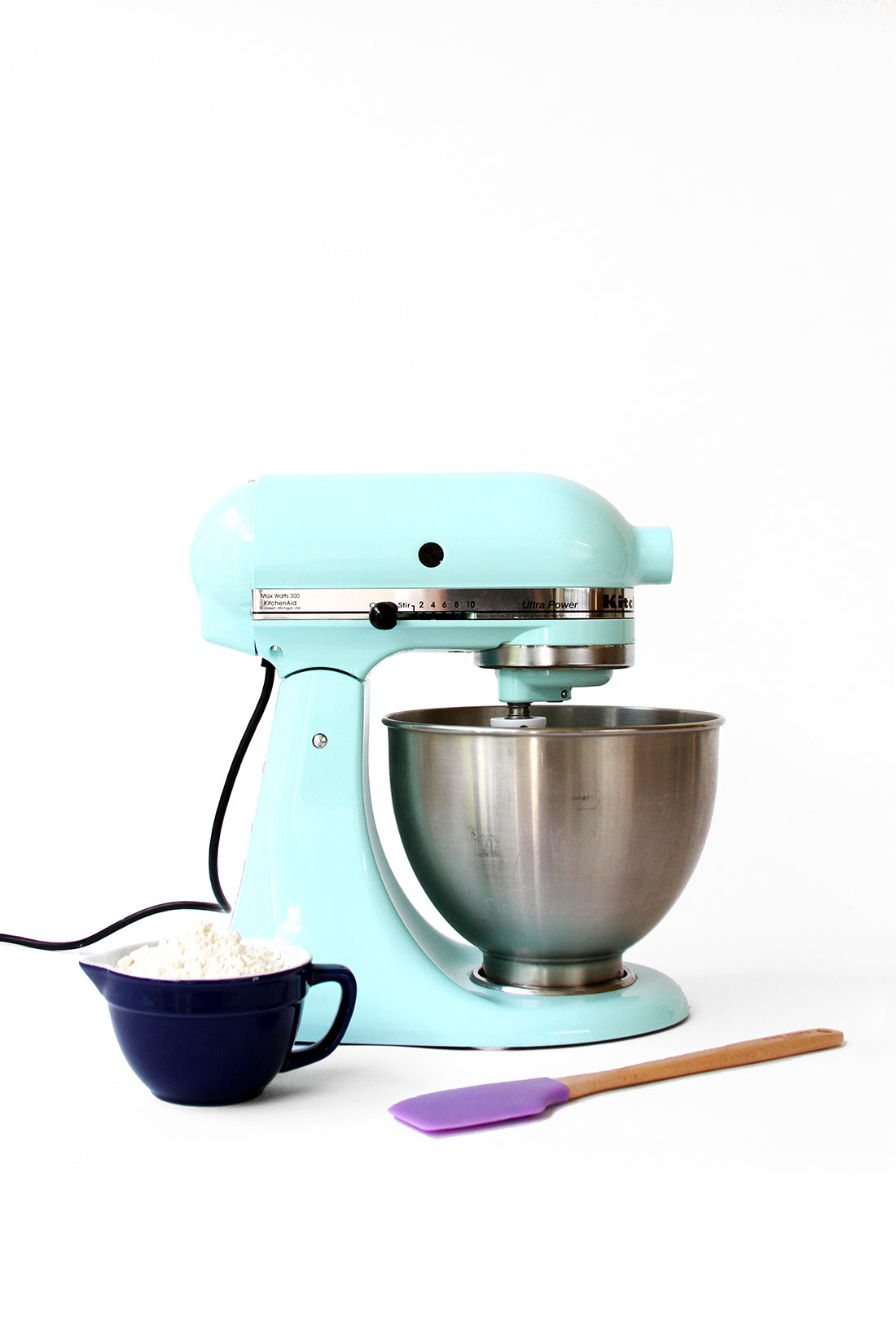 Image of side of blue kitchen aid next to spatula and ingredients for Miss Jones Baking Co Cake Mix Cinnamon Rolls
