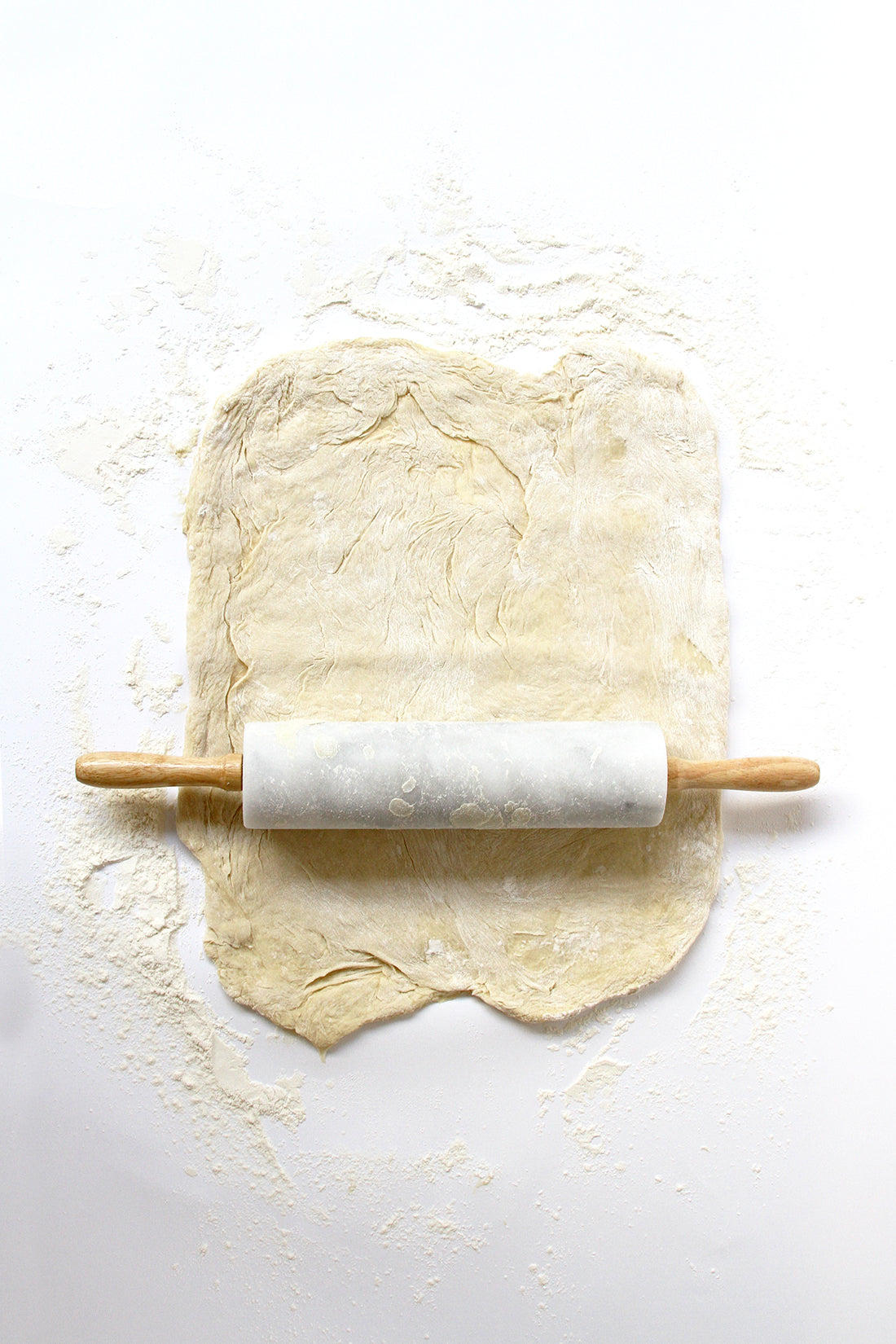 Image of dough for Miss Jones Baking Co Cake Mix Cinnamon Rolls Recipe being spread out with a rolling pin