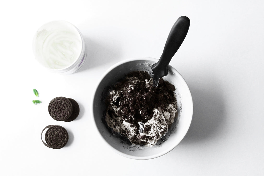 Image from above of sandwich cookies in a bowl with two on the side next to a bowl of cream for Miss Jones Baking Co Minty Cookie Crunch Cake
