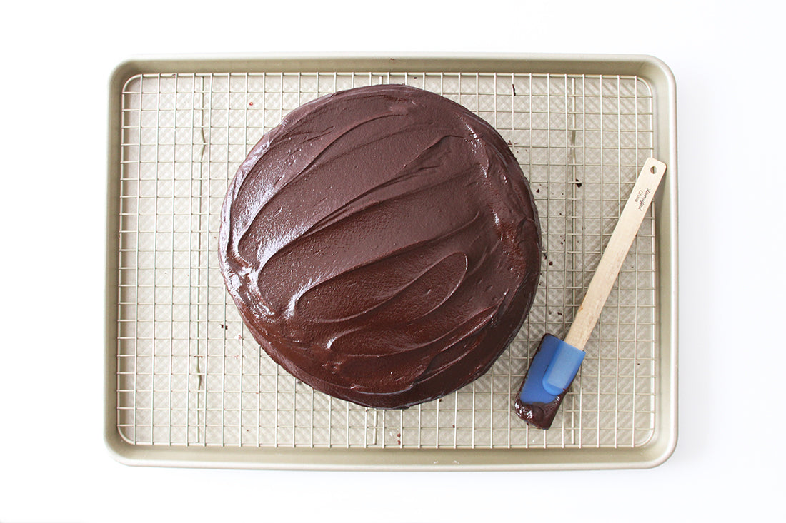 Image of the top of Miss Jones Baking Co Minty Cookie Crunch Cake on a baking rack next to a blue spatula