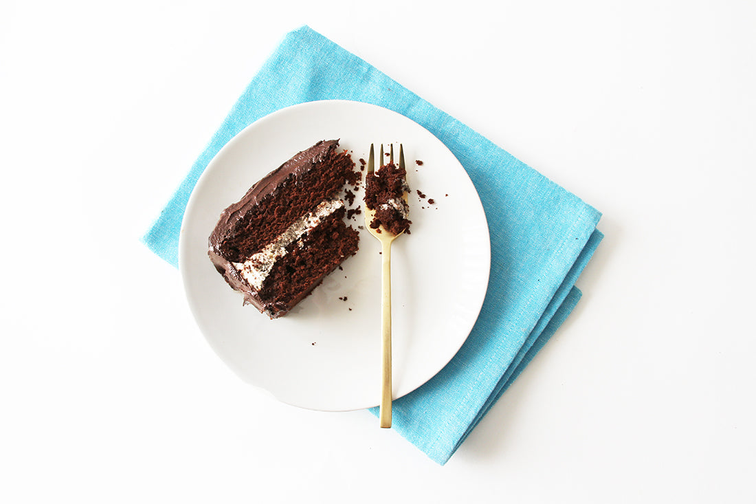 Image from above of a slice of Miss Jones Baking Co Minty Cookie Crunch Cake on a white plate next to a gold fork