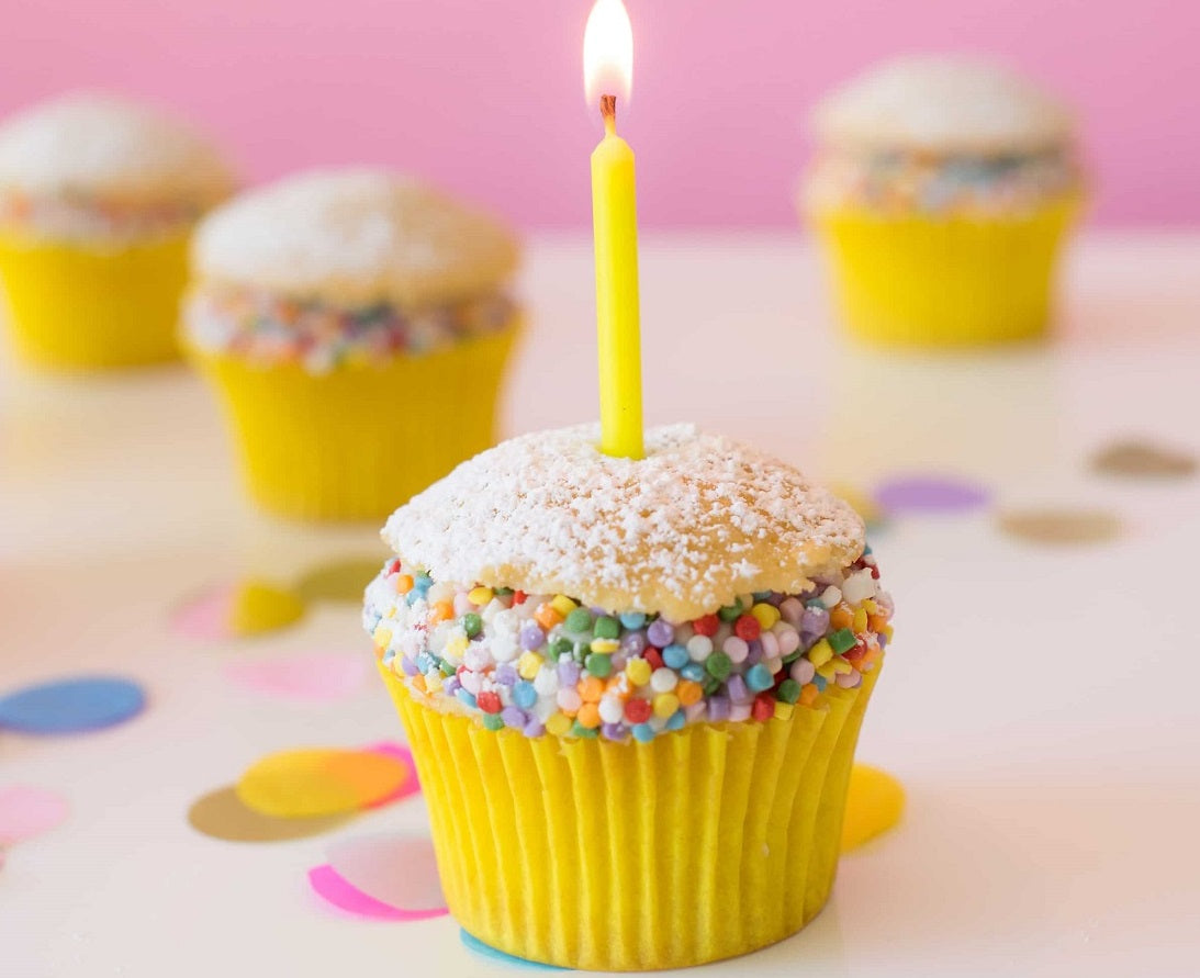 playful cupcakes with sprinkles and candle
