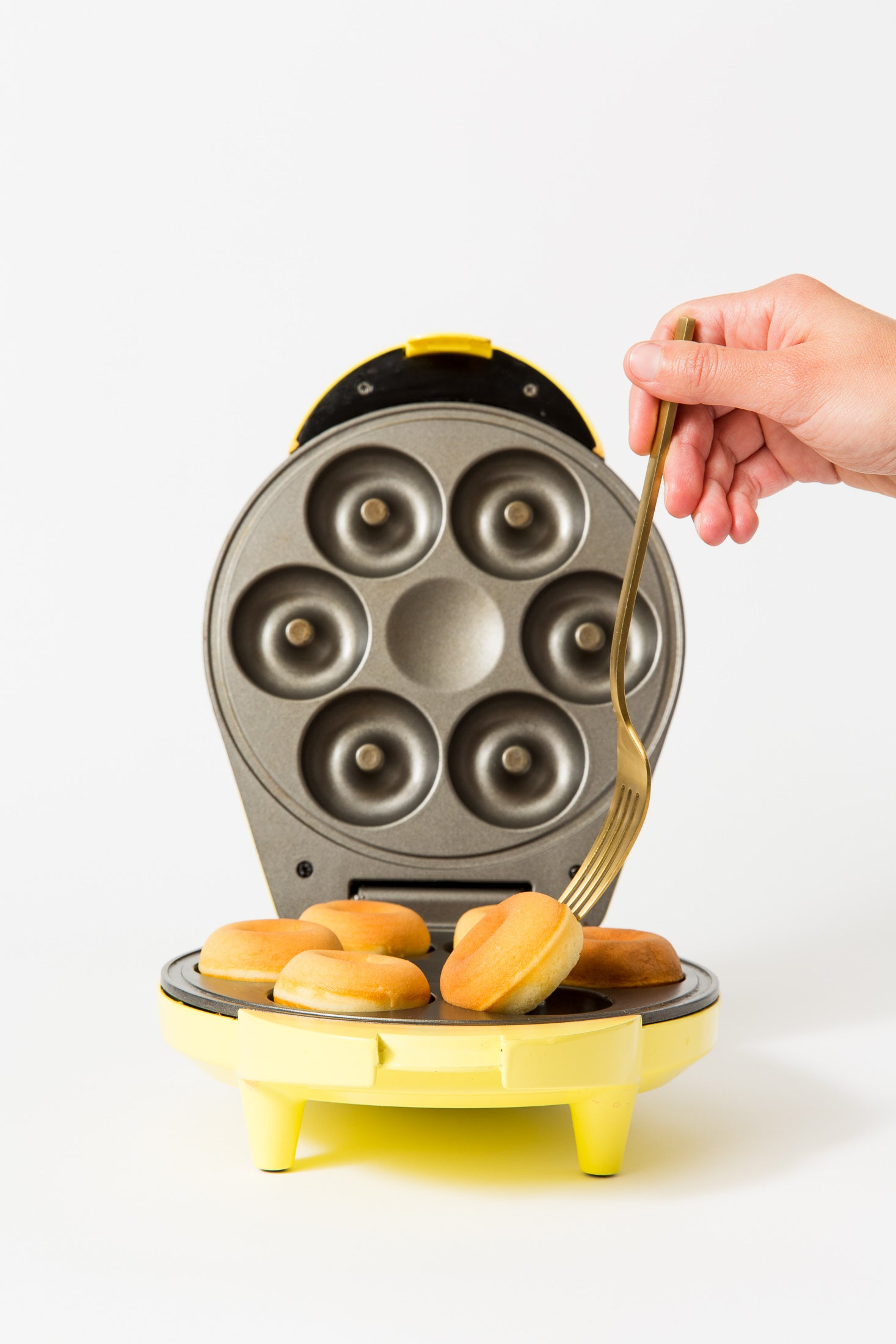 Image of a donut maker with six Miss Jones Baking Co Dirty Chai Mini Donuts being pulled out by a fork