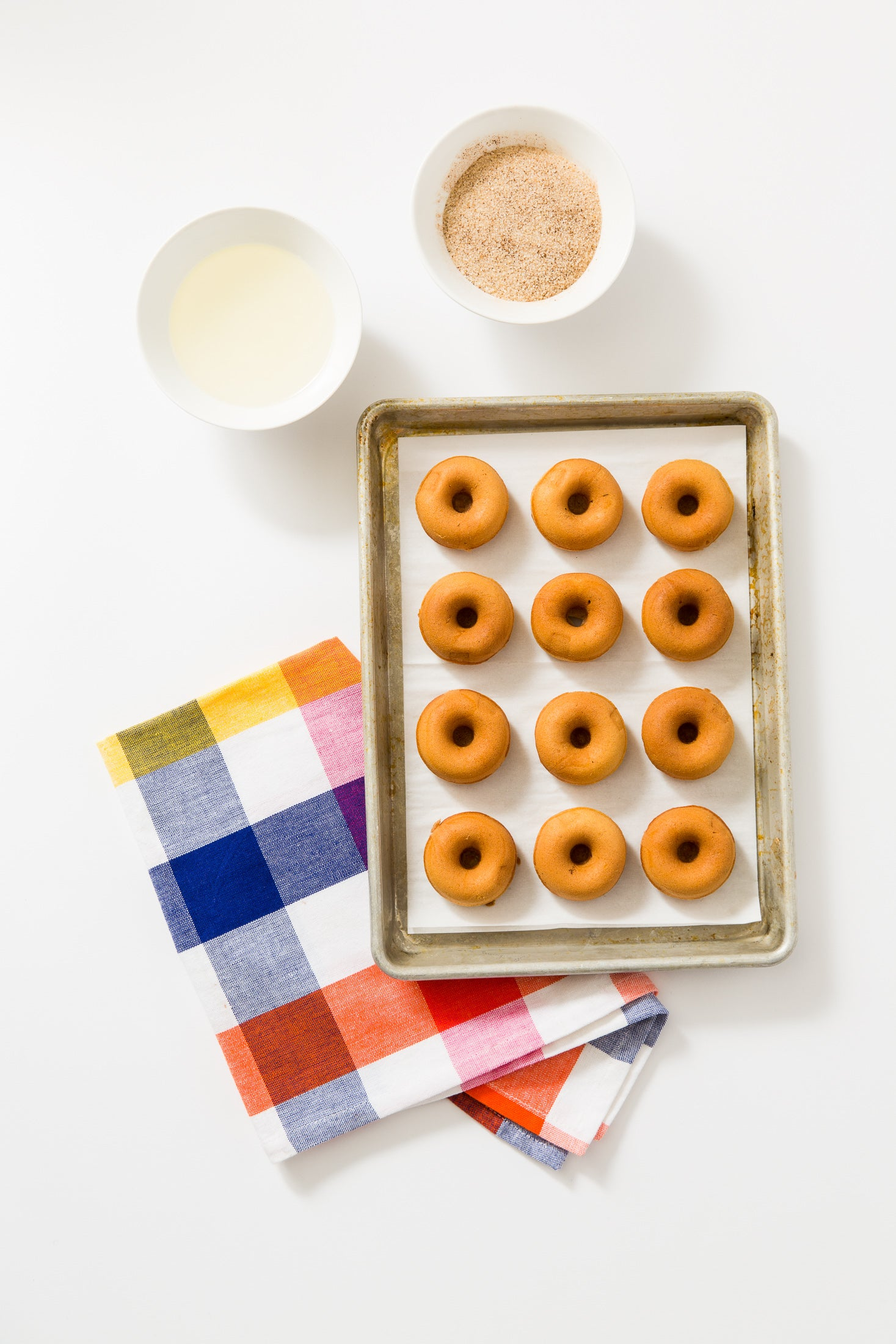 Image of twelve Miss Jones Baking Co Dirty Chai Mini Donuts on a baking sheet next to a bowl of milk and a bowl of cinnamon sugar