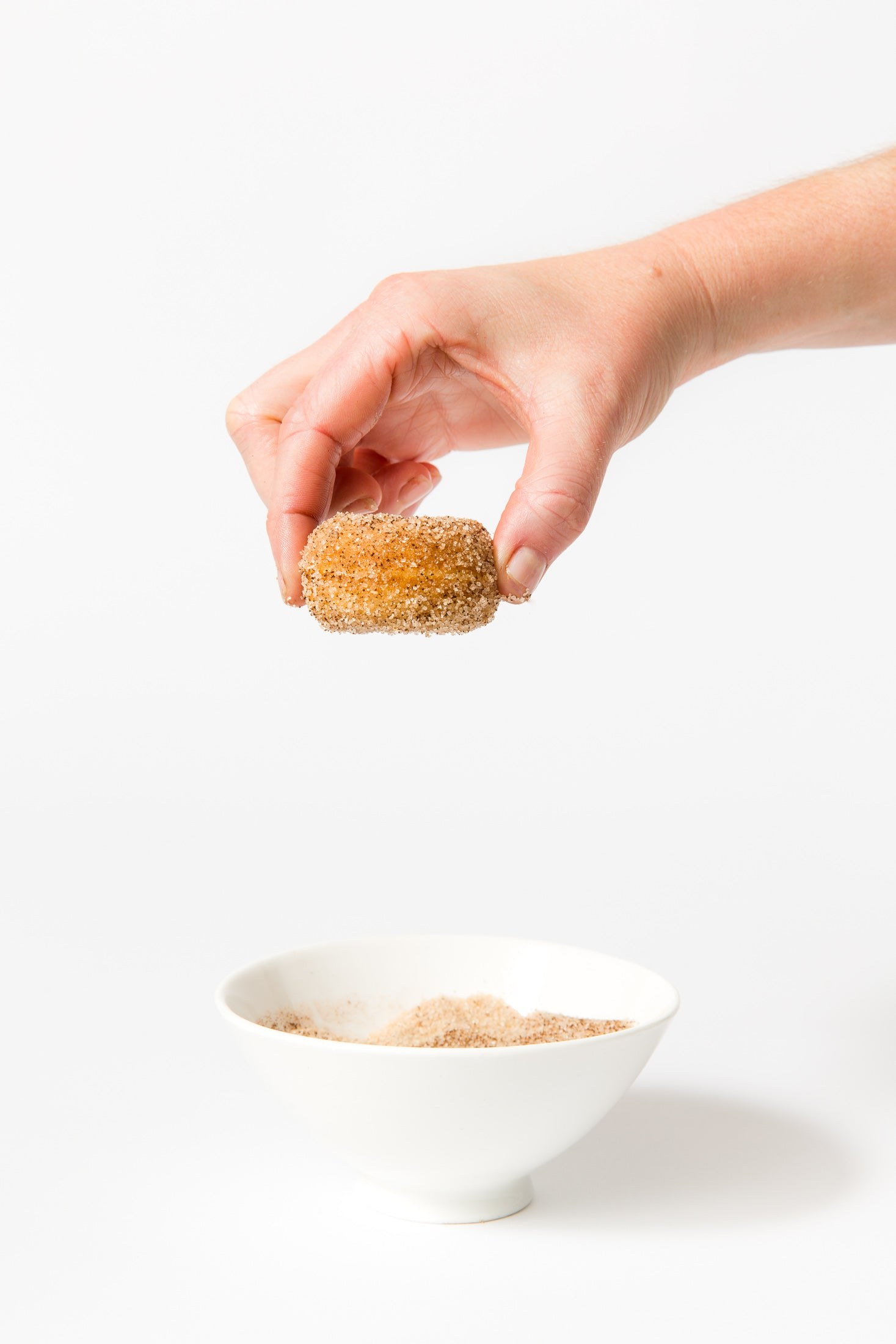 Image of a hand holding a Miss Jones Baking Co Dirty Chai Mini Donut above a bowl of cinnamon sugar
