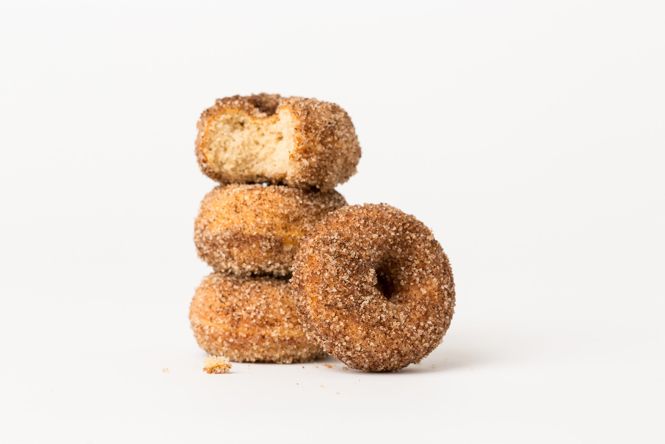 A Miss Jones Baking Co Dirty Chai Mini Donut leaning against a stack of three Miss Jones Baking Co Dirty Chai Mini Donuts with the top donut missing a bite