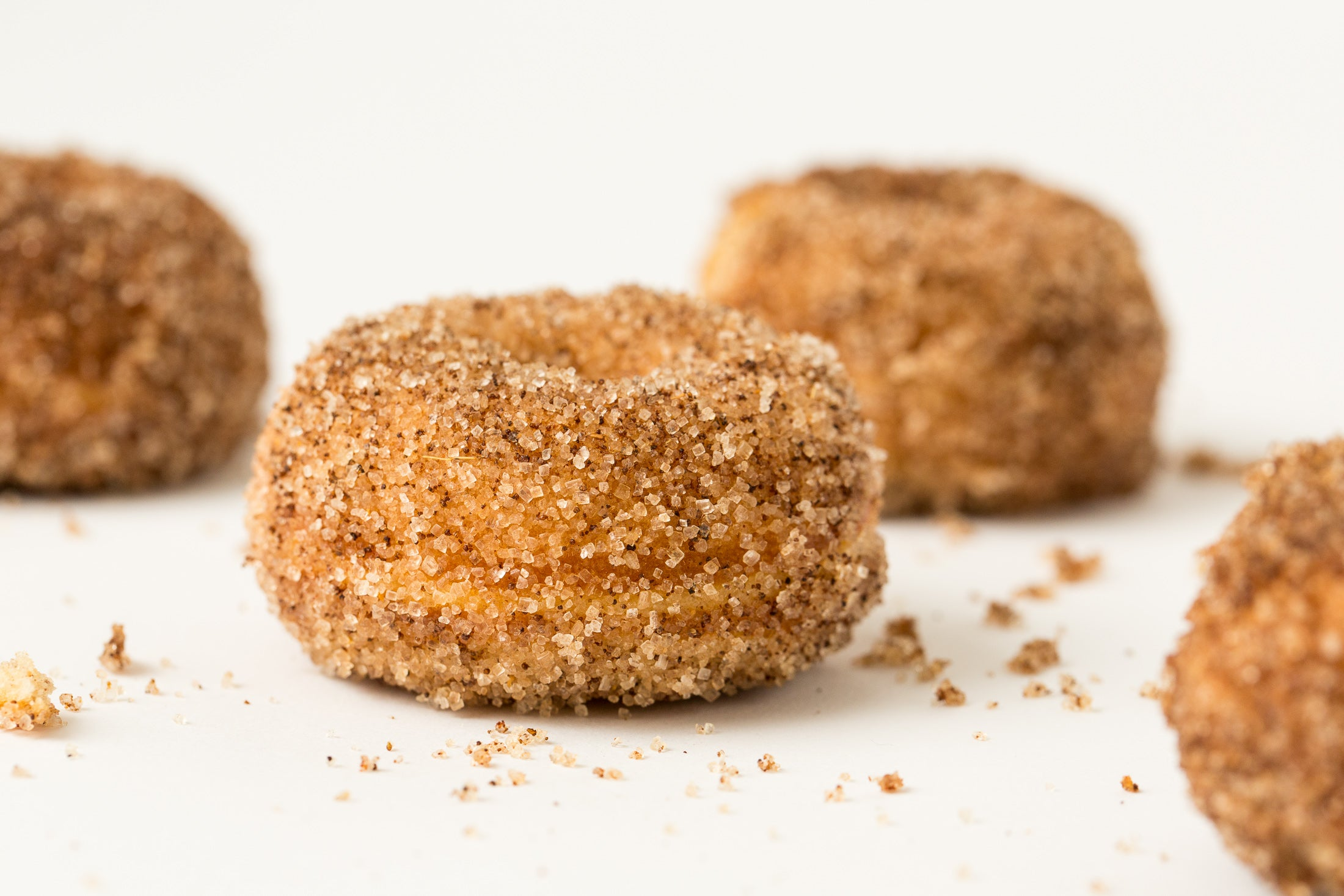 Close up image of four Miss Jones Baking Co Dirty Chai Mini Donuts from the side