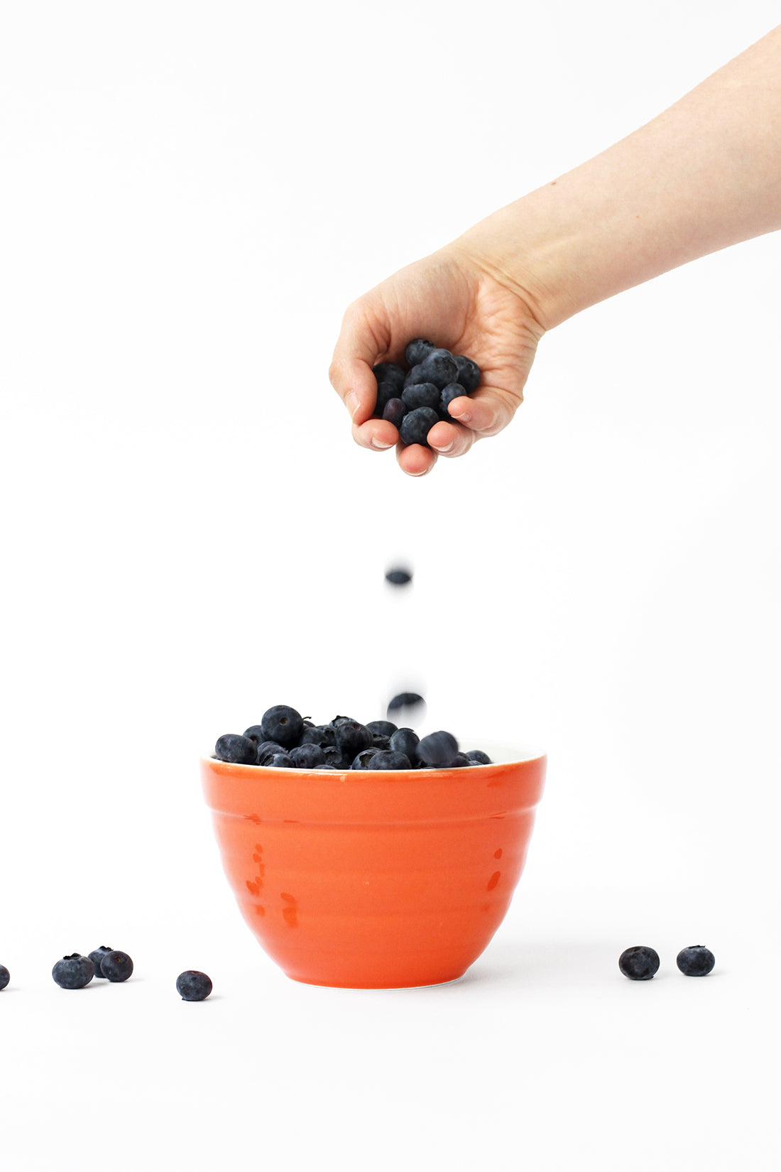 Image of a hand dropping blueberries into an orange bowl used for Miss Jones Baking Co Firecracker Pops recipe