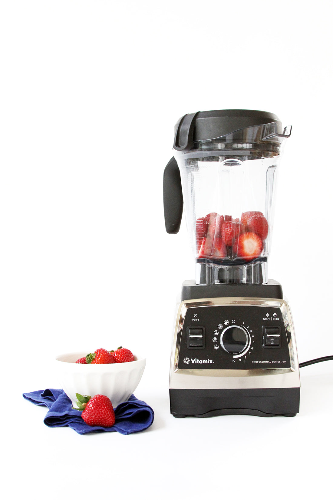 Image of strawberries in a blender next to a bowl of strawberries used for Miss Jones Baking Co Firecracker Pops recipe