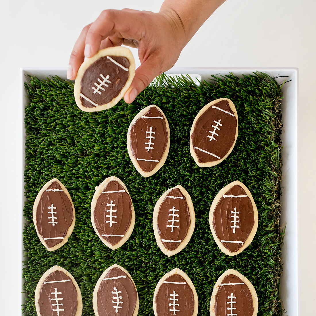 Image from above of eleven Miss Jones Baking Co Soft & Chewy Football Cutout Sugar Cookies on a turf mat