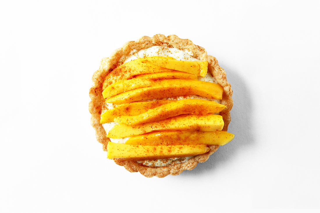 Image of top of a Miss Jones Baking Co Fruit Cart Tart topped with mango slices