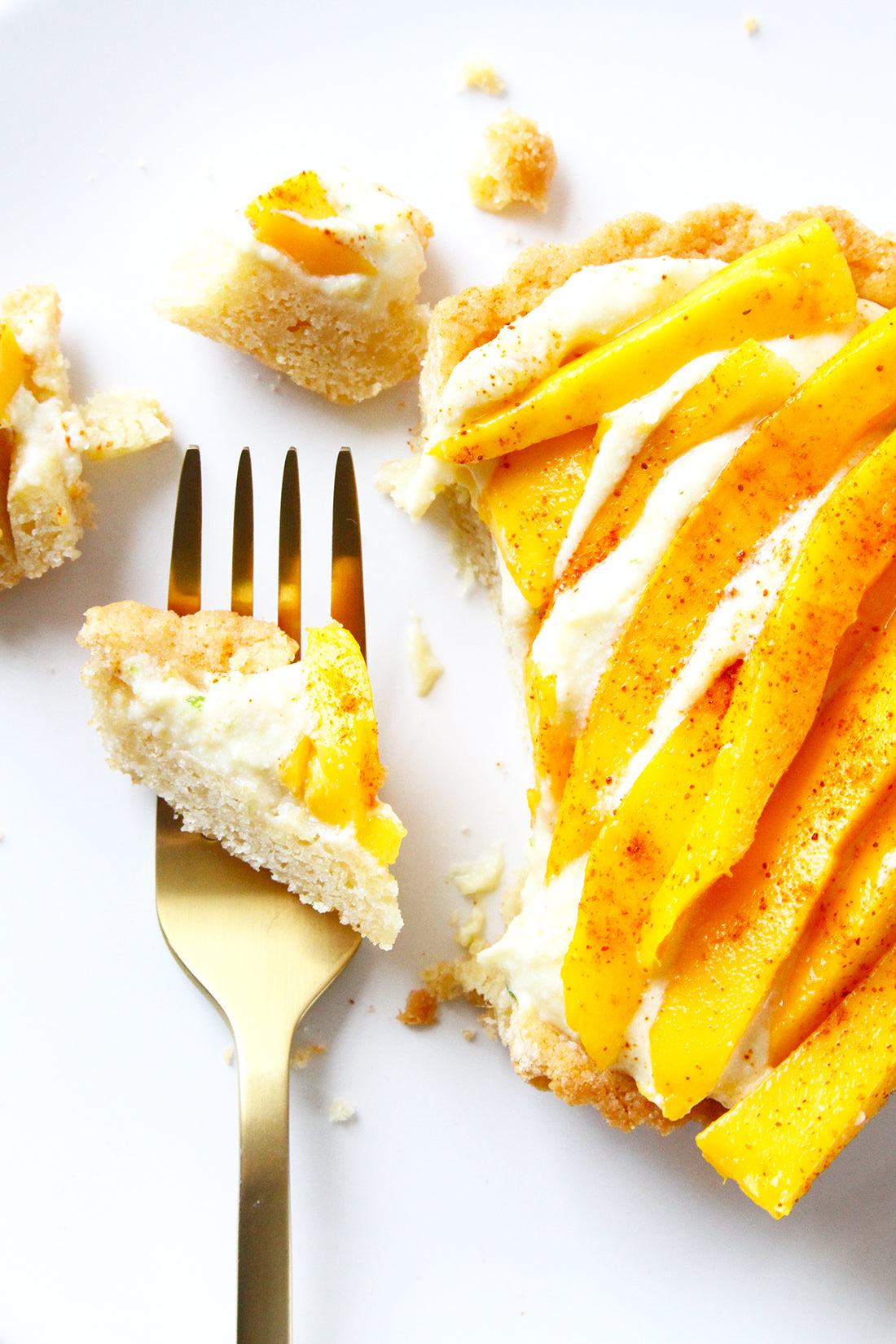 Close up image of part of a Miss Jones Baking Co Fruit Cart Tart next to a fork with a bite on it