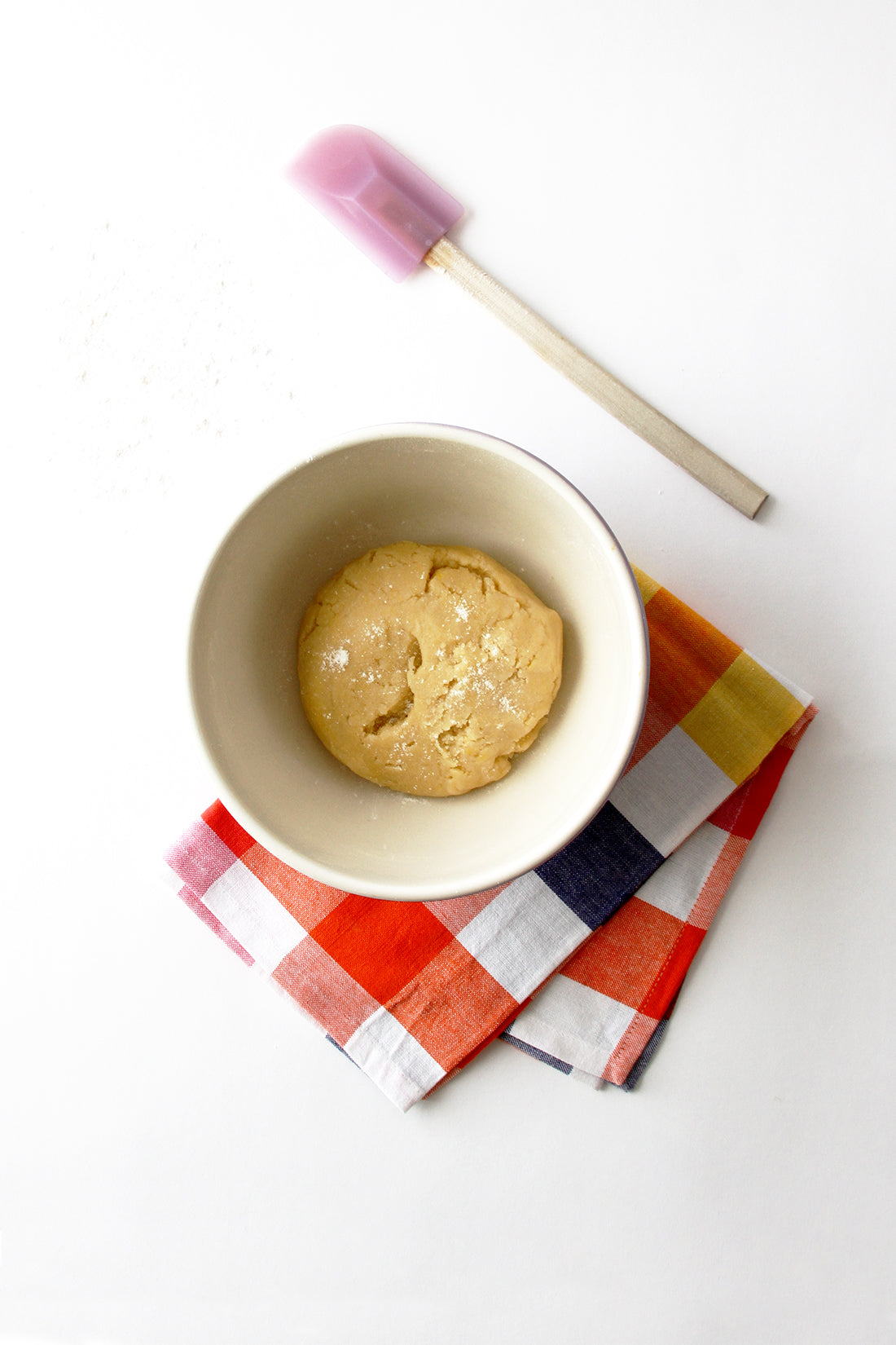 Image of the top of Miss Jones Baking Co Fruit Cart Tarts dough in a bowl above a towel and next to a purple spatula