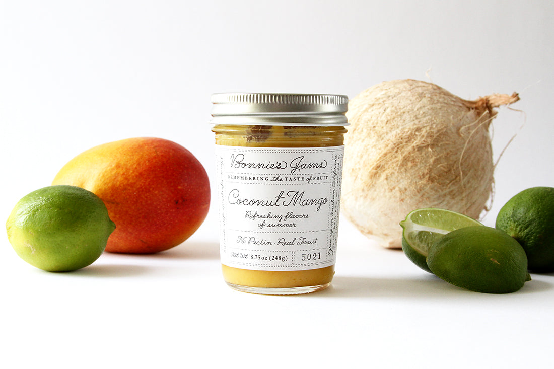 Image of side of a jar of Bonnie's Jams Coconut Mango flavored next to a coconut, a few limes, and a mango used for Miss Jones Baking Co Fruit Cart Tarts recipe
