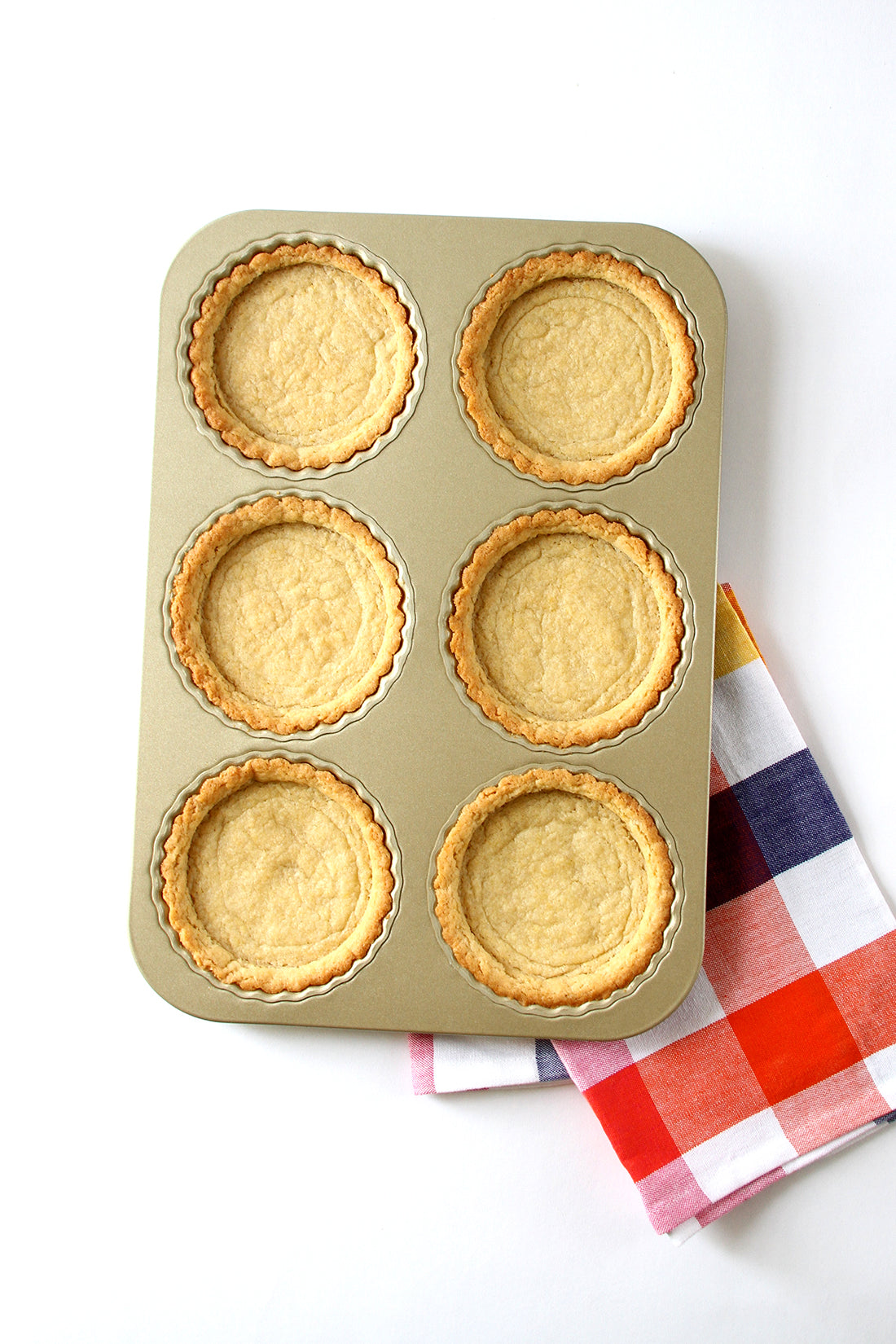 Image of six tart crusts in a baking pan on top of a checkered towel for Miss Jones Baking Co Fruit Cart Tarts recipe