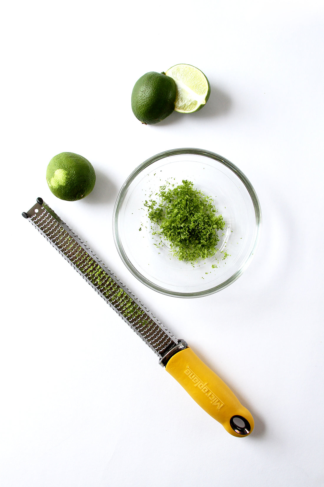 Image of lime zest in a bowl next to limes and a zester for Miss Jones Baking Co Fruit Cart Tarts recipe