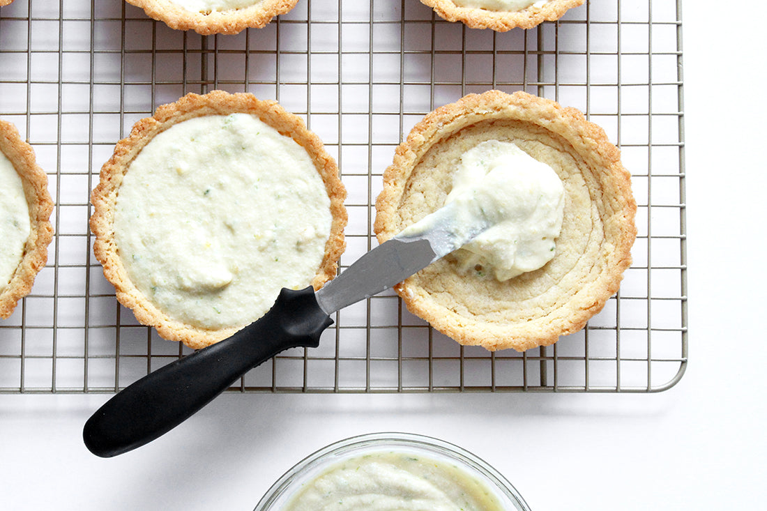 Image of filling being spread in two tart crusts on a baking rack used for Miss Jones Baking Co Fruit Cart Tarts recipe