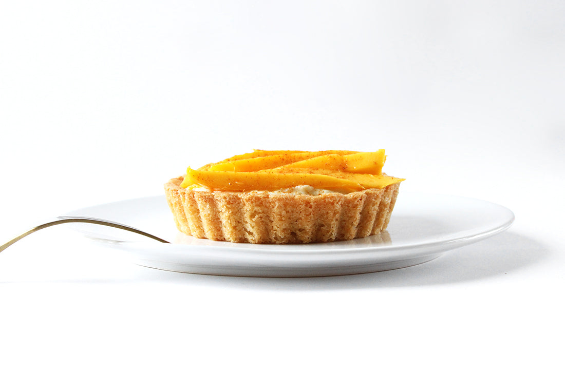 Image of side of a Miss Jones Baking Co Fruit Cart Tart on a white plate with a fork