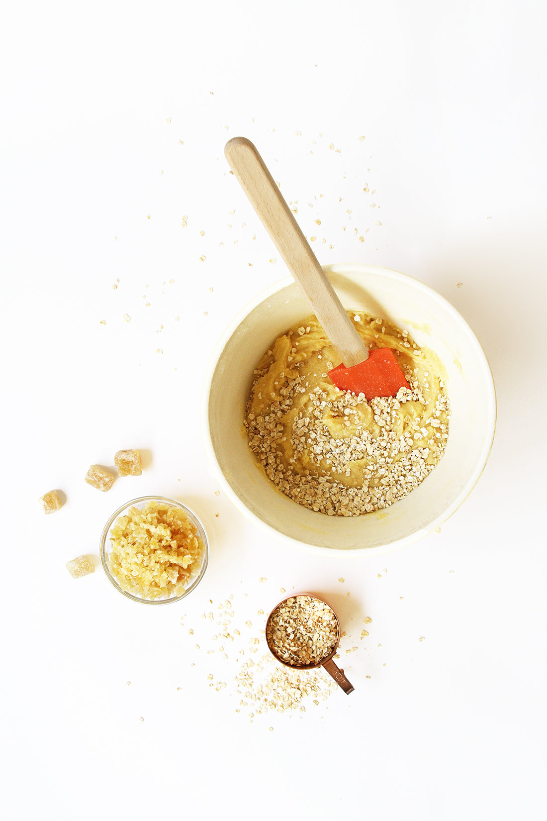Image of a bowl of Miss Jones Baking Co Ginger Oatmeal Drop Cookies batter next to a measuring cup of oats and a bowl of ginger