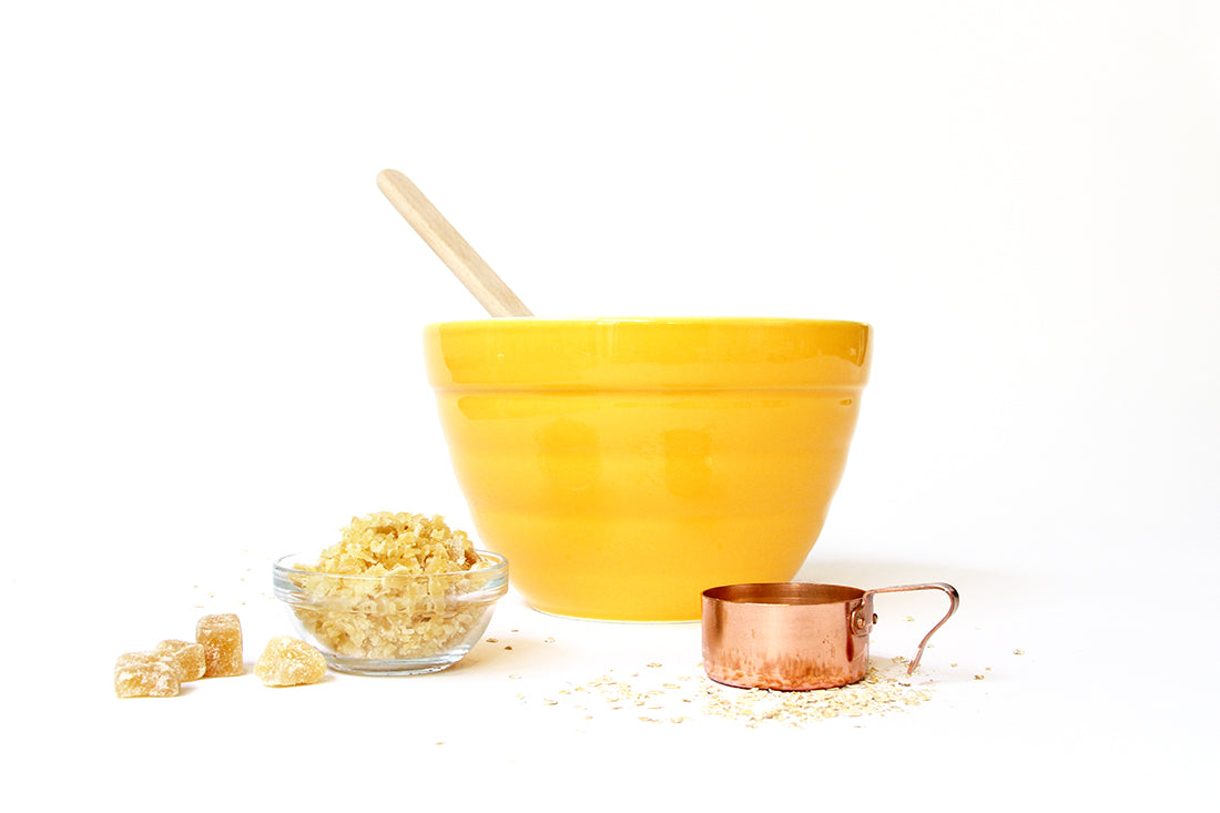 Image of the side of a yellow mixing bowl next to a glass bowl of ginger and a measuring cup of oats for Miss Jones Baking Co Ginger Oatmeal Drop Cookies