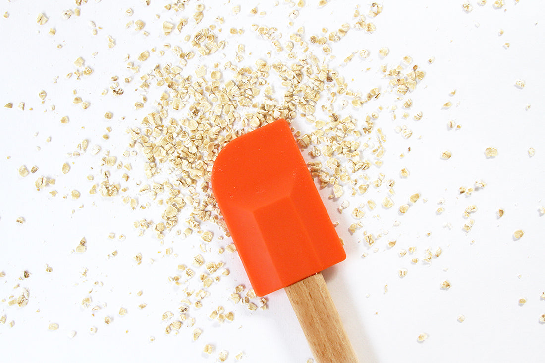 Image of an orange spatula above scattered oats for Miss Jones Baking Co Ginger Oatmeal Drop Cookies recipe