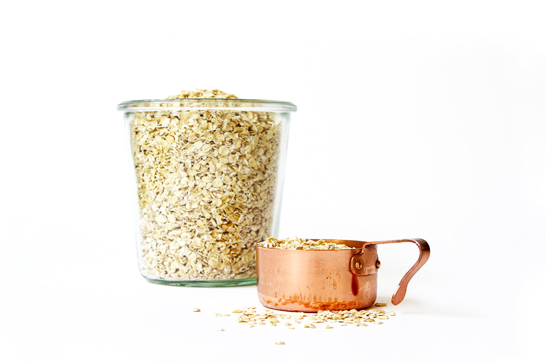 Image of oats in a glass jar next to a coper measuring cup full of oats used for Miss Jones Baking Co Ginger Oatmeal Drop Cookies recipe