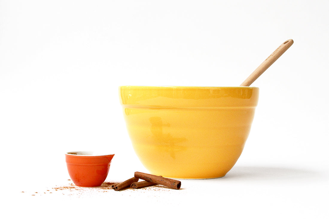 A large yellow mixing bowl next to a small orange bowl and some cinnamon sticks used for Miss Jones Baking Co Classic Hummingbird Cake
