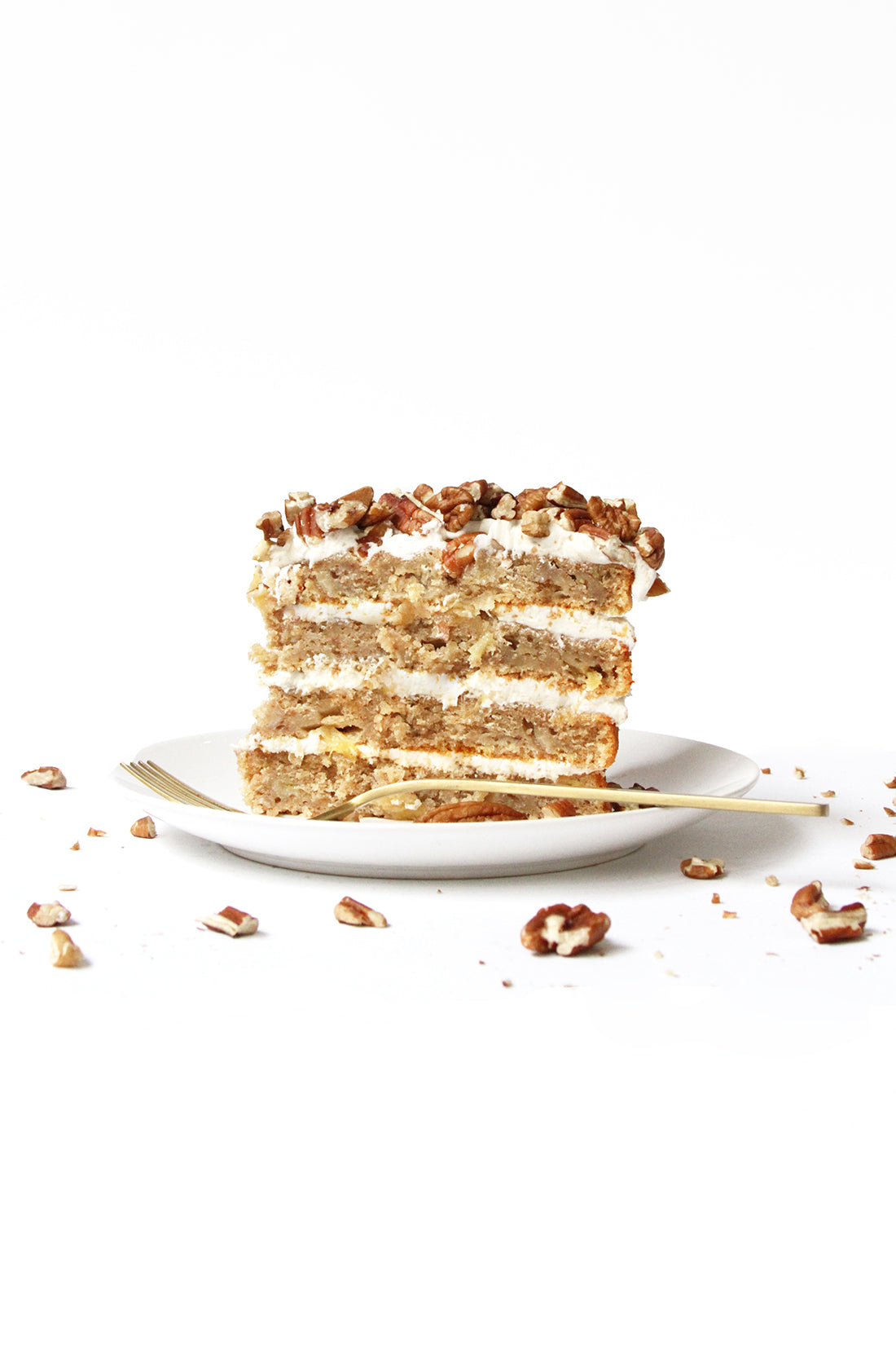 Image of side of a slice of Miss Jones Baking Co Classic Hummingbird Cake on a white plate