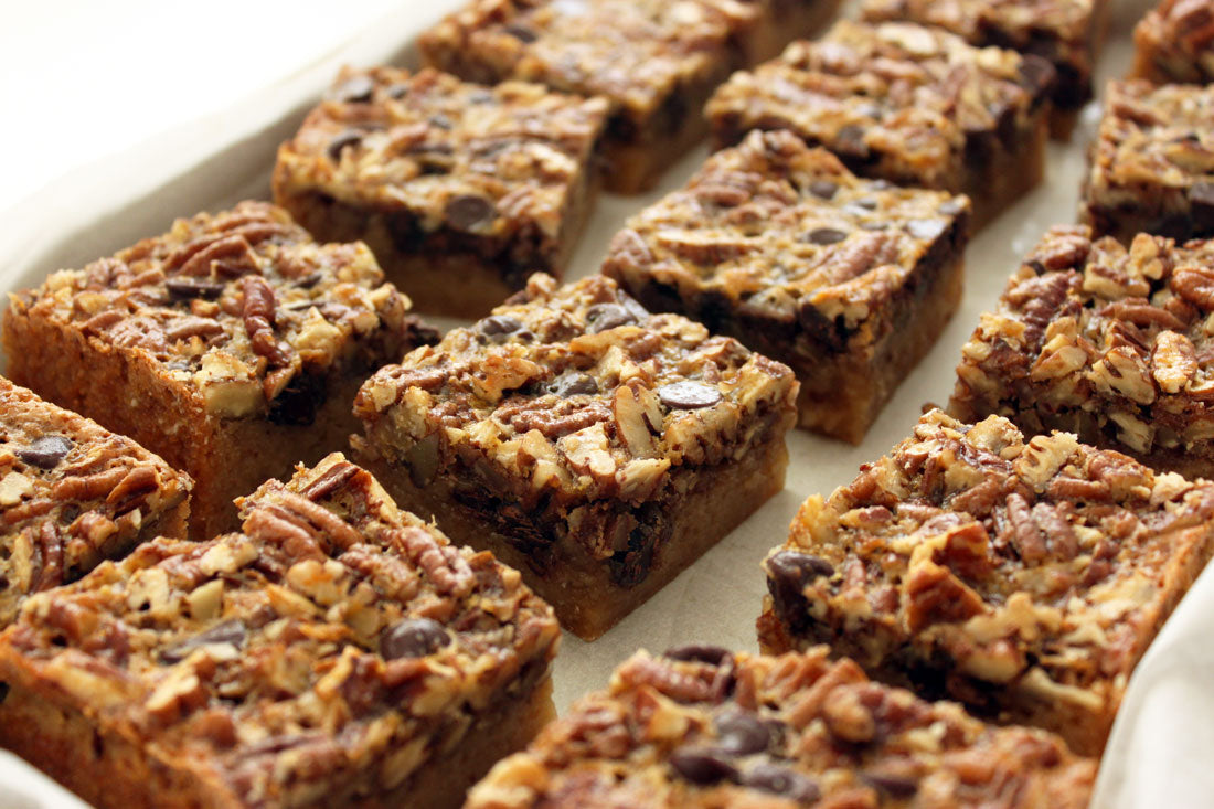 Close up image of Miss Jones Baking Co Chocolate Pecan Pie Butter Bars on a baking sheet lined with parchment paper