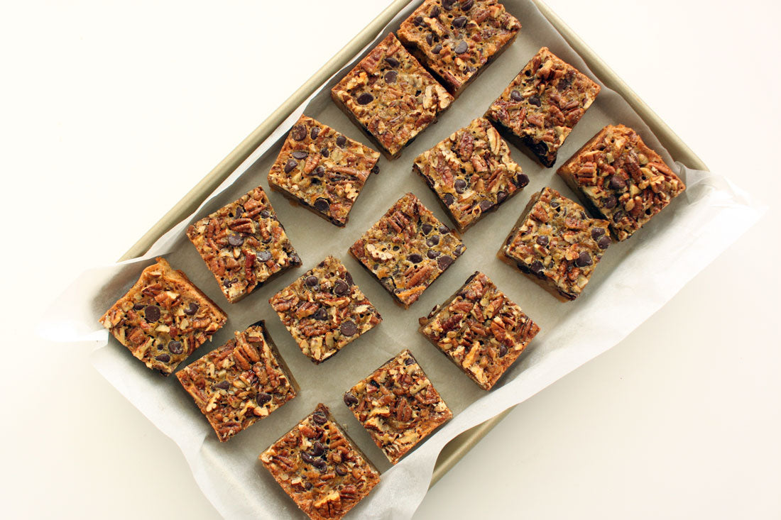 Fifteen Miss Jones Baking Co Chocolate Pecan Pie Butter Bars on a baking sheet lined with parchment paper