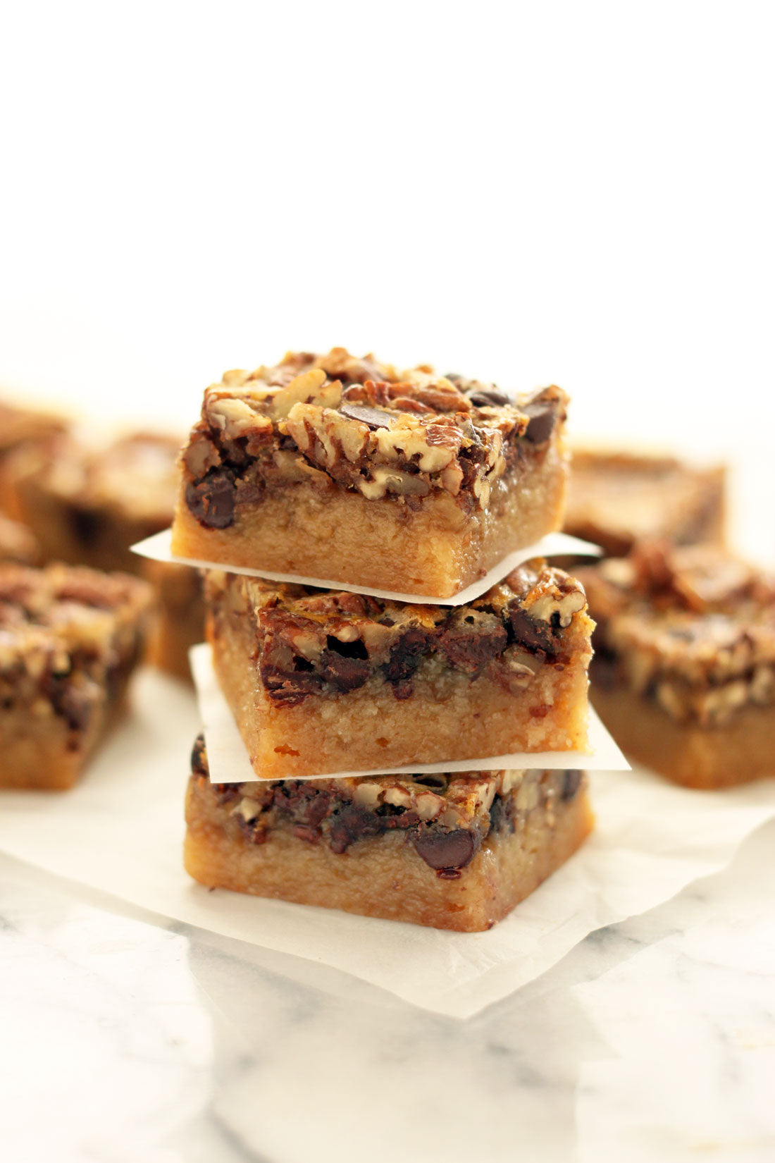 Image of three Miss Jones Baking Co Chocolate Pecan Pie Butter Bars stacked in front of other Miss Jones Baking Co Chocolate Pecan Pie Butter Bars