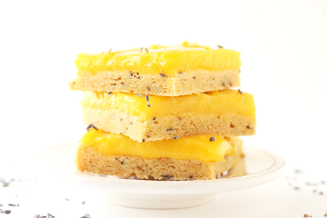 Image of the side of a stack of three Miss Jones Baking Co Lavender Lemon Bars on a plate