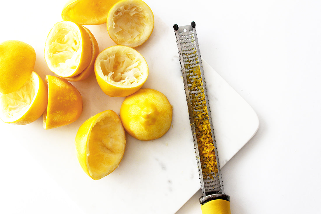 Image from above of part of a cutting board with juiced and zested lemon halves next to a zester with lemon zest on it for Miss Jones Baking Co Lavender Lemon Bars recipe